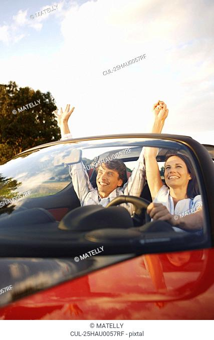 Couple in an electric sports car, fun