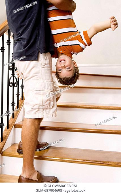 Man carrying his son upside down on a staircase