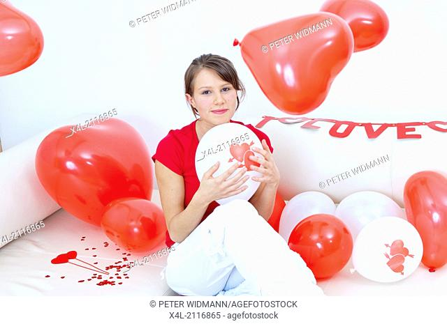 Young woman with hearts and balloons, I love you garland (model-released)
