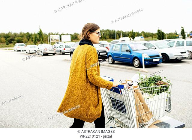 Side view of young woman pushing trolley full of purchases towards car park