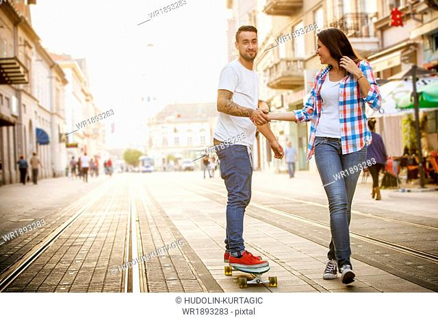 Young man skateboarding on city street, woman assisting