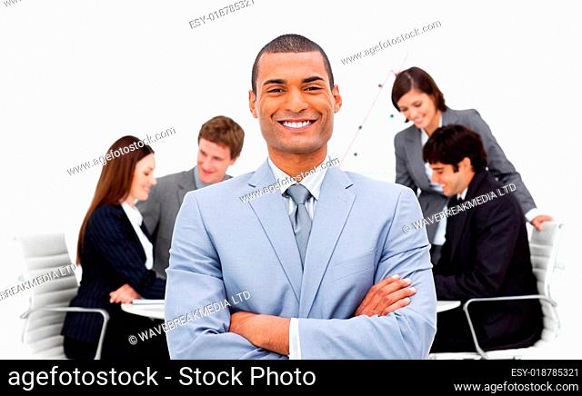 Ethnic businessman sitting in front of his team