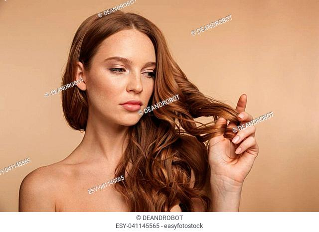 Beauty portrait of pretty ginger woman with long hair touching her hair and looking away over cream background