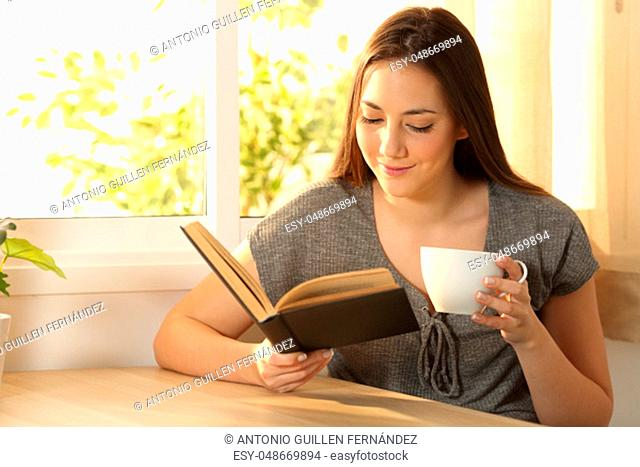 Relaxed woman reading a paper book and holding a cup of coffee sitting in a table at home with a warm light