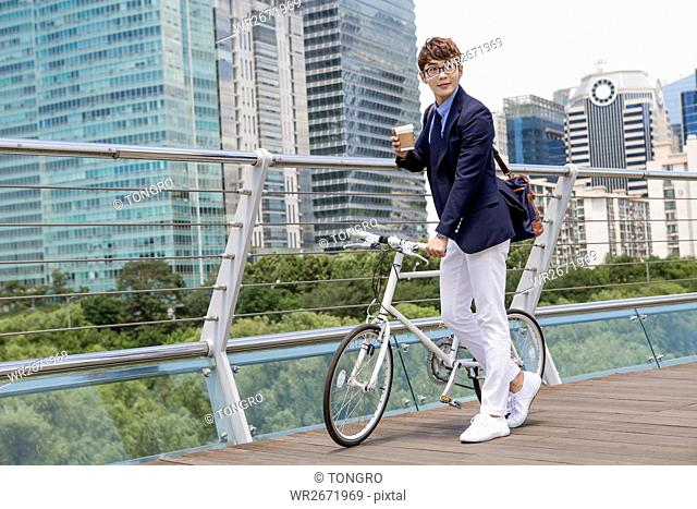 Smiling businessman with takeout coffee and bicycle posing