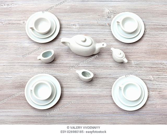 food concept - top view of cups with saucers and tea set on gray brown table