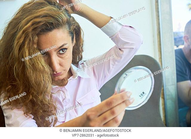 mature woman examining her face in mirror