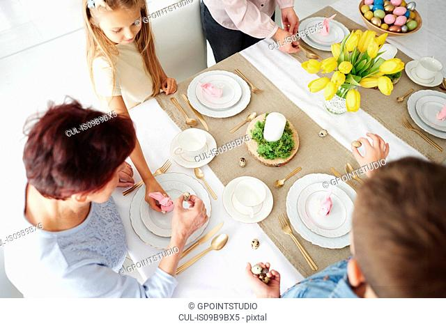 Overhead view of grandmother and family preparing easter dining table