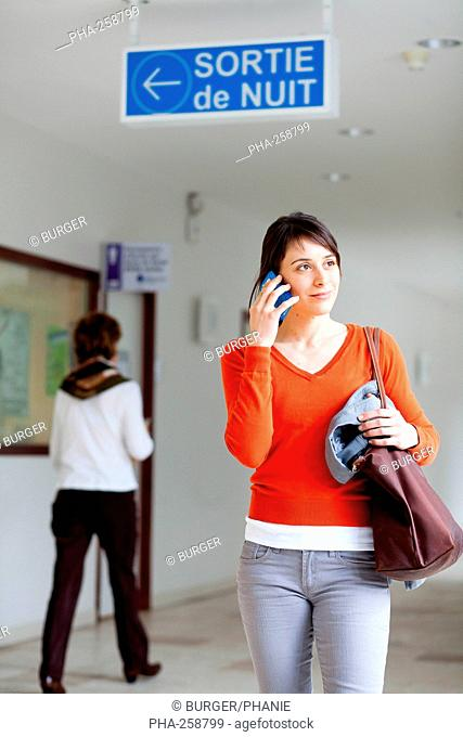 Woman using cell phone in a hospital corridor