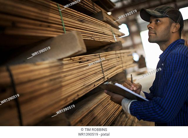 A heap of recycled reclaimed timber planks of wood. Environmentally responsible reclamation in a timber yard. A man with a clipboard by a rack of planks