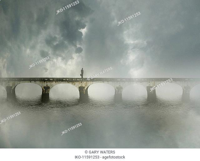 Businessman standing alone on bridge in fog