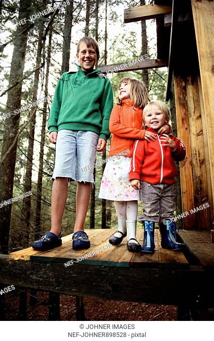 Three children playing in the forest, Sweden