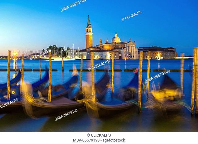 Riva degli Schiavoni, Venice, Veneto, Italy. Moored gondolas in front of St George's church