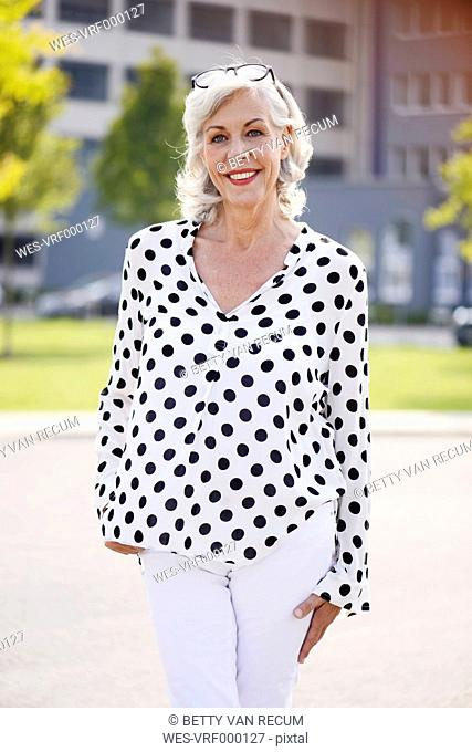 Portrait of smiling senior woman wearing white blouse with black dots