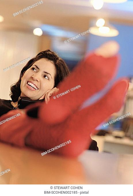 Young woman talking on phone with hole in sock