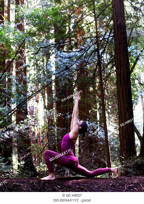Mid adult woman doing yoga in forest, in low lunge pose