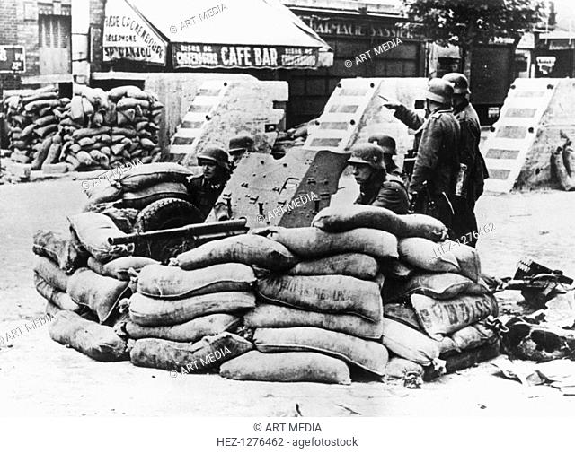 German soldiers with captured French barricade, near Paris, June 1940. The first German troops entered Paris, which had been declared an open city by the French...