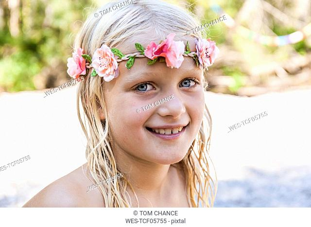 Portrait of smiling girl wearing flower crown outdoors in summer