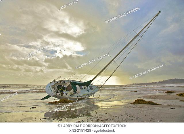 As the storm that ran it aground clears, a sailboat lies high and dry on East Beach, Santa Barbara, California, United States
