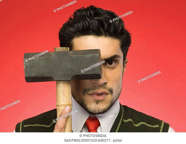 Portrait of a businessman holding a sledgehammer in front of his face
