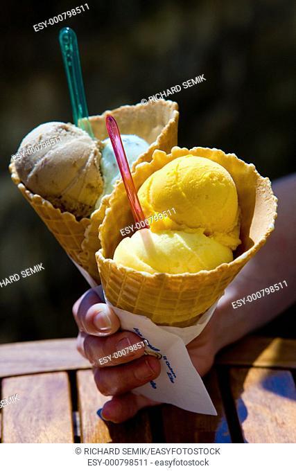 hand holding cones with ice cream