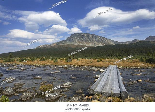 Concrete footbridge over river in remote landscape