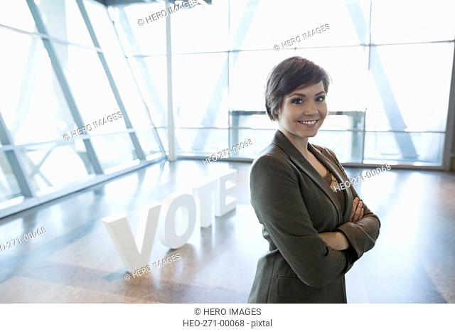 Portrait confident young businesswoman near Vote text
