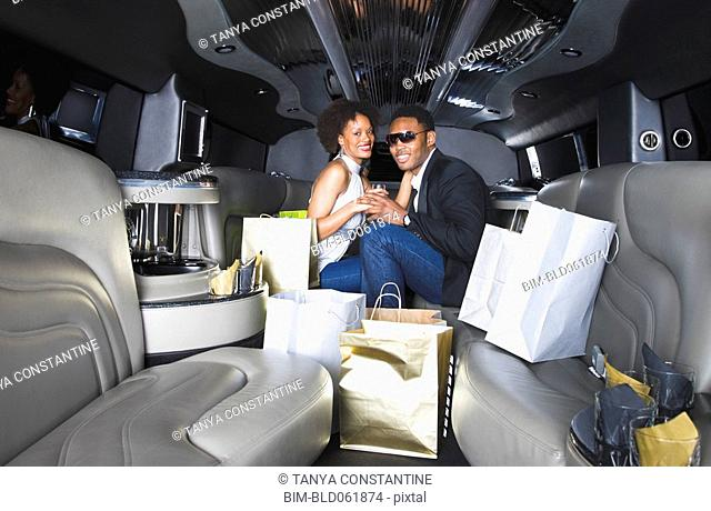 African couple with shopping bags in limousine