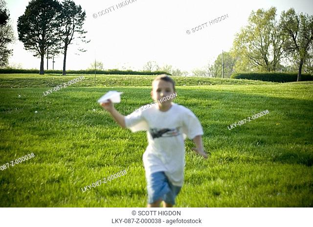 Boy running with paper plane, out of focus