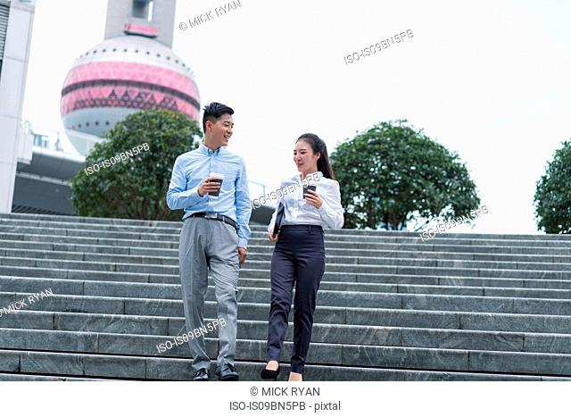 Young businesswoman and man with takeaway coffee moving down city stairway, Shanghai, China