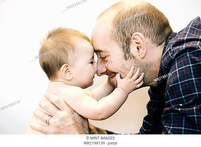 A young baby girl and her father face to face playing