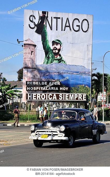 Vintage car driving in front of revolutionary propaganda poster, Santiago siempre heróica, Spanish for Santiago is always heroic, Plaza de la Revolucion