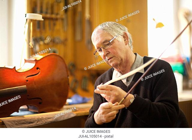 Senior violin maker putting hair on violin bow