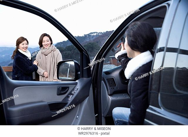 Three middle aged women going on winter vacation in a car
