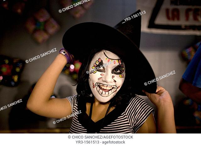 A girl with her face painted and a witch hat smiles and posses during the 16th International Clown Convention: The Laughter Fair organized by the Latino Clown...