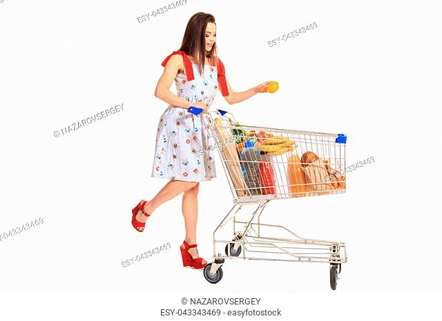 Young woman with full shopping cart on white background. Brunette in a summer dress makes purchases, isolated on white. Full-length photo