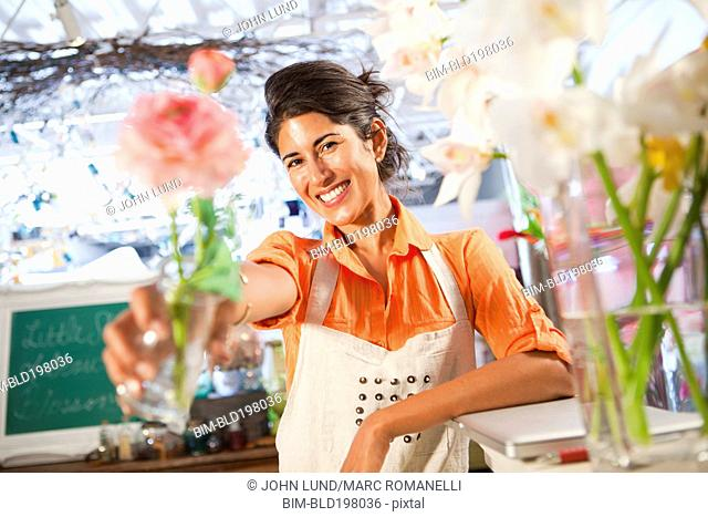Hispanic florist holding out flower in flower shop