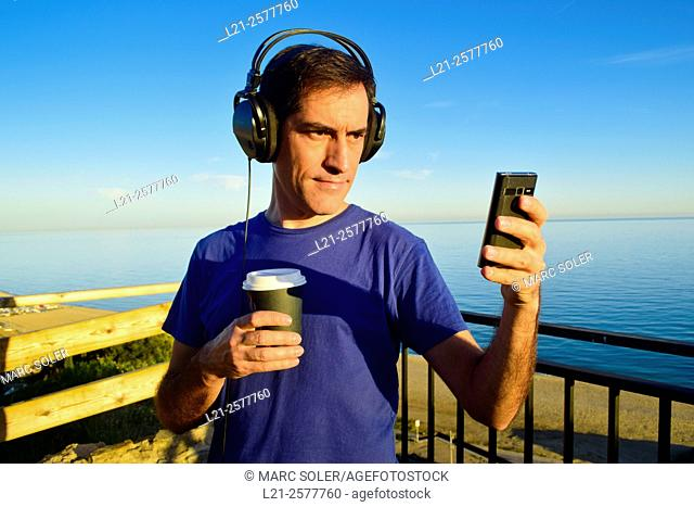 Man with blue t-shirt is listening music with his headphones on while he is using a mobile phone and is holding a plastic cup of coffee outdoor near the sea