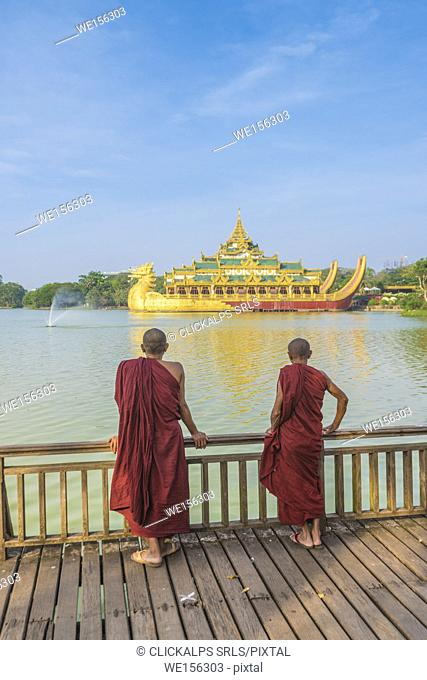 Yangon, Myanmar (Burma). Two monks watching the Karaweik Palace on the Kandawgyi Lake