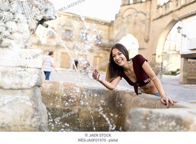 Spain, Baeza, portrait of laughing young woman splashing with water of a fountain