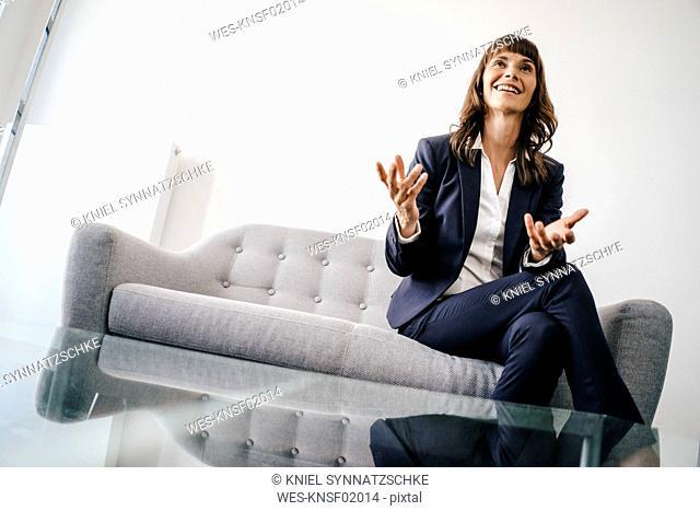 Businesswoman sitting on couch, gesturing
