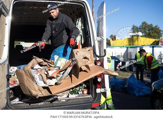 A showman removing waste paper from a car at the recycling depot of the Cannstatt Volksfest in Stuttgart, Germany, 05 October 2017
