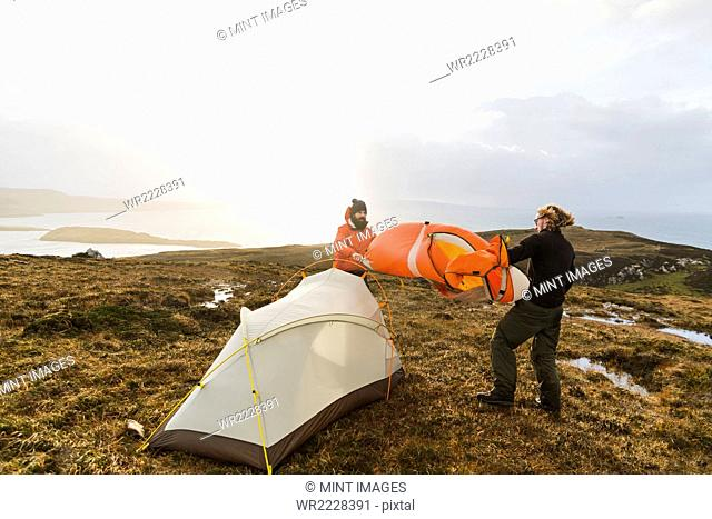 Two men holding and putting up a small tent in open space. Wild camping