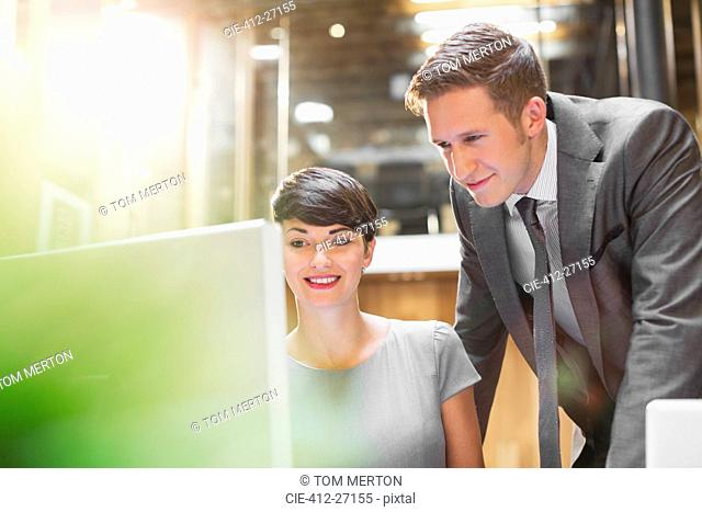 Businessman and businesswoman using computer in office