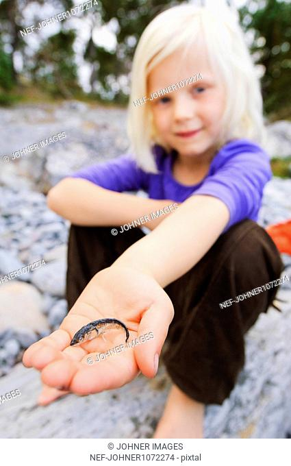 Portrait of girl holding fish on beach