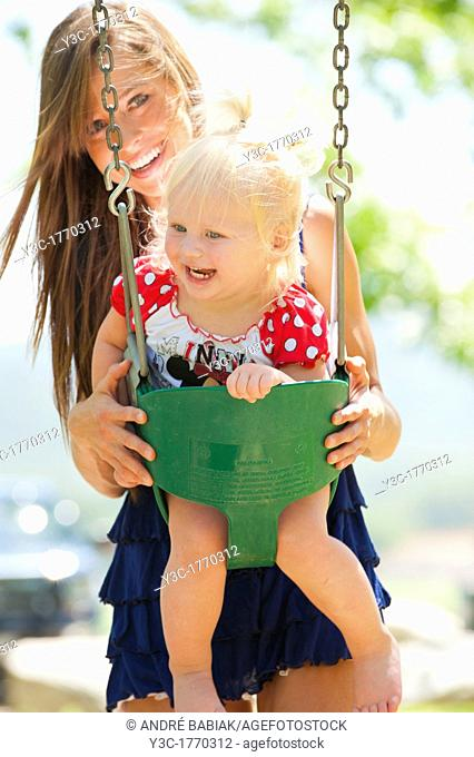 Young mother with two years old female child on a swing in a park