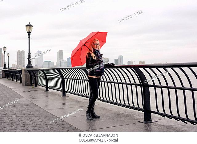 Female tourist with red umbrella looking out over East River, New York, USA