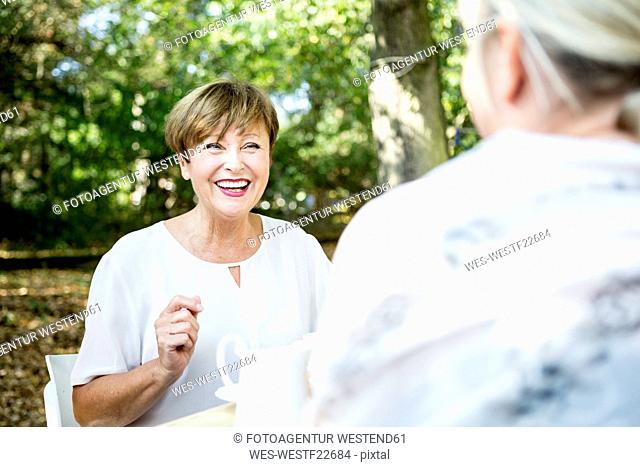 Happy senior woman socializing with friend outdoors