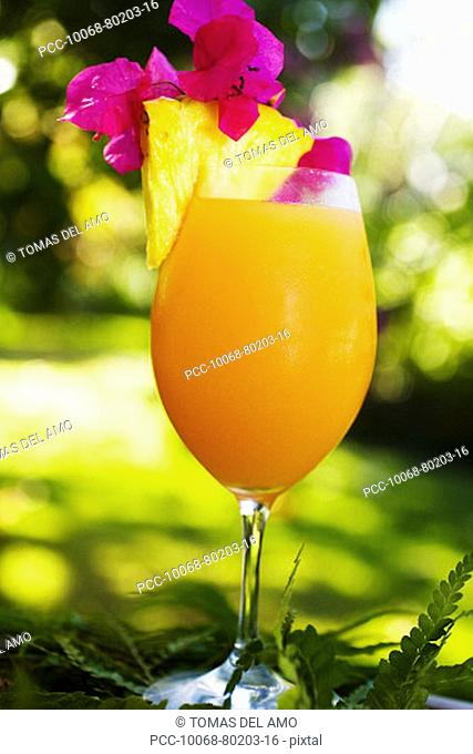 A tropical cocktail garnished with fruit in an outdoor setting