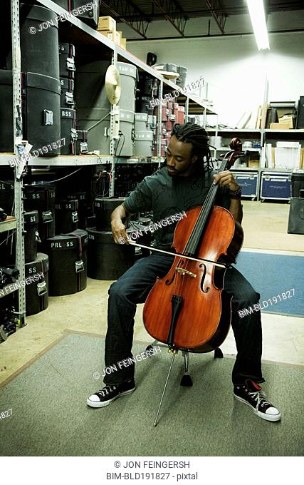 African man playing cello in warehouse
